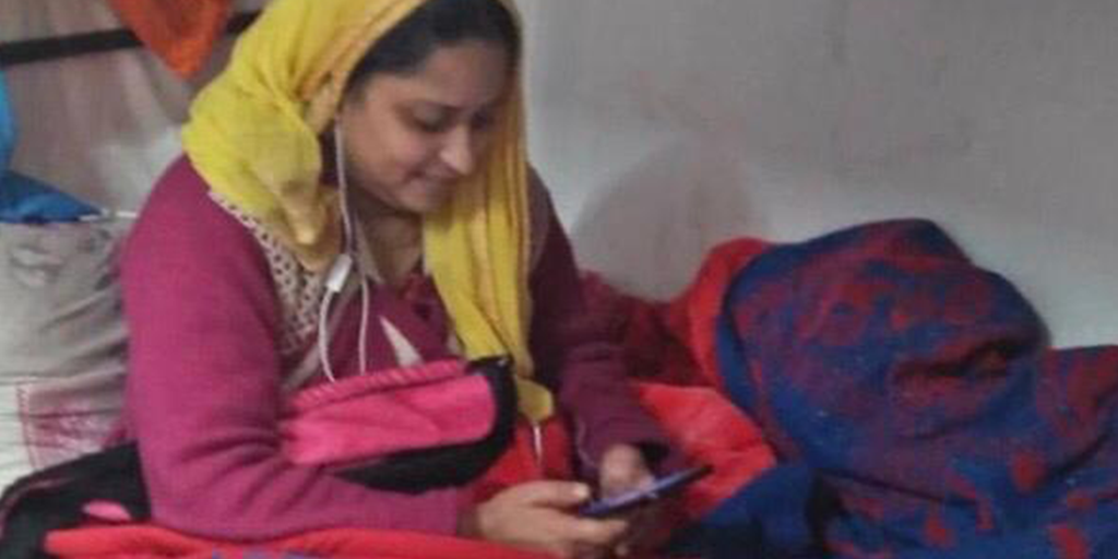 Due to COVID-19, migrant workers in the garment sector in Jordan spend time talking to family members on their mobile phones.